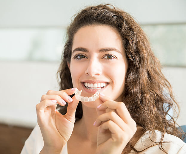 woman putting in her teeth aligners